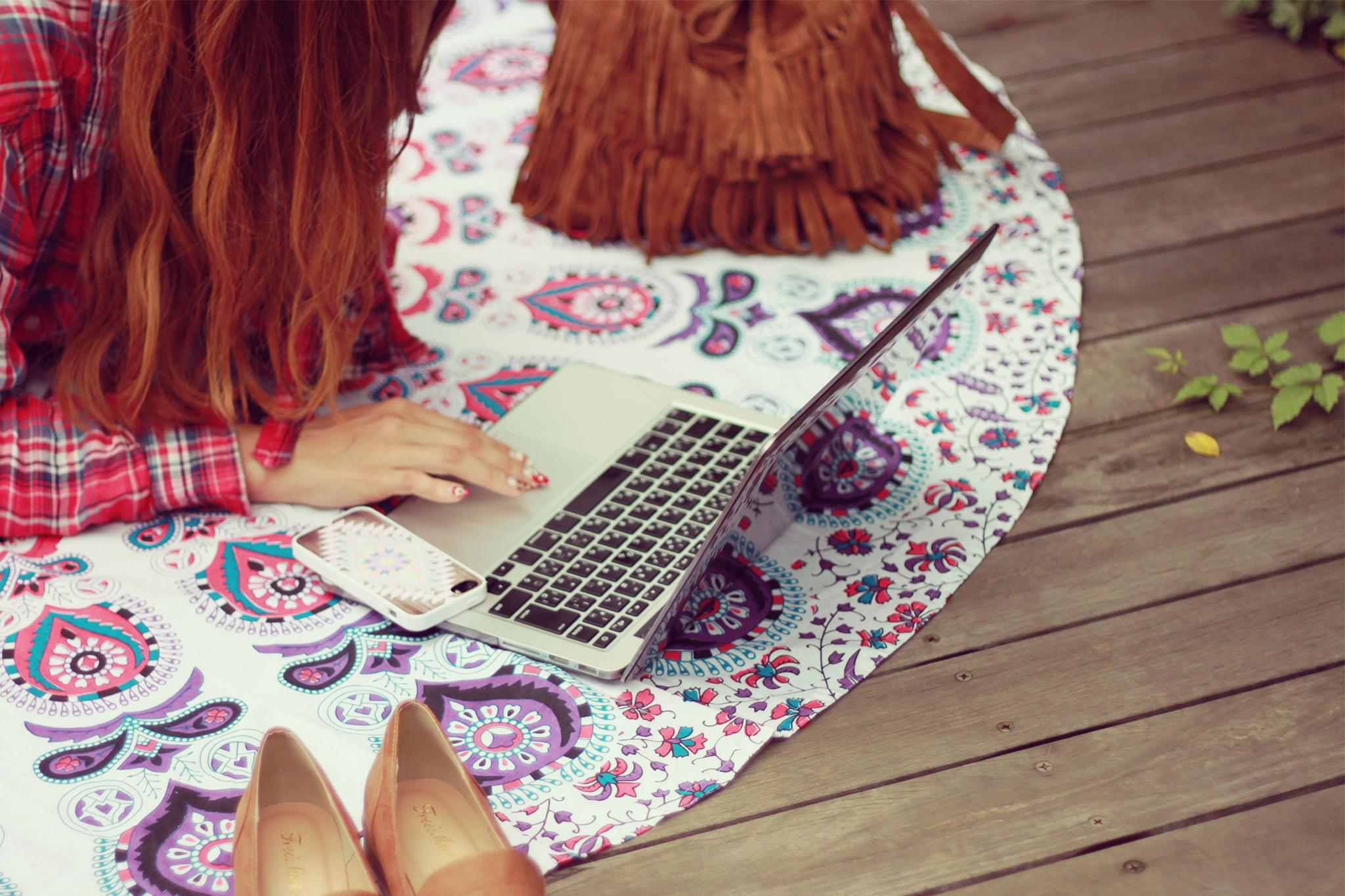 外でパソコンを広げ、青空コーディングをする女の子